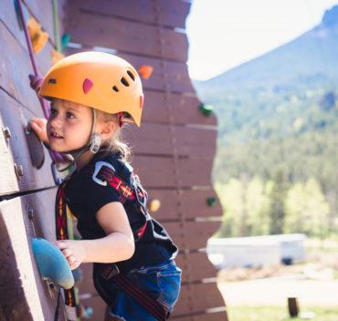 Little girl scaling a climbing wall