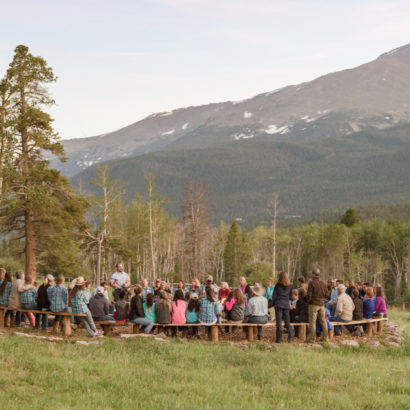 People gathered around a firepit staring out at the mountains