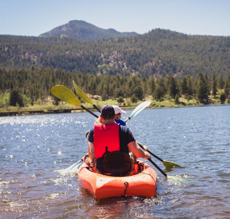 A couple kayaking on a lake together.