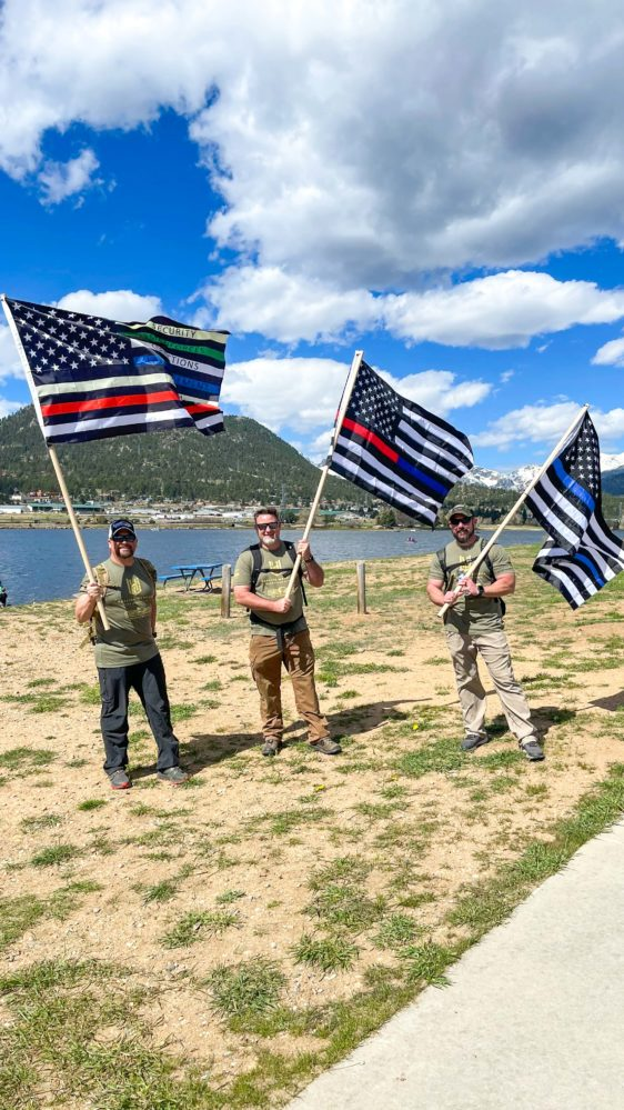 Three men holding three variations of the American flag