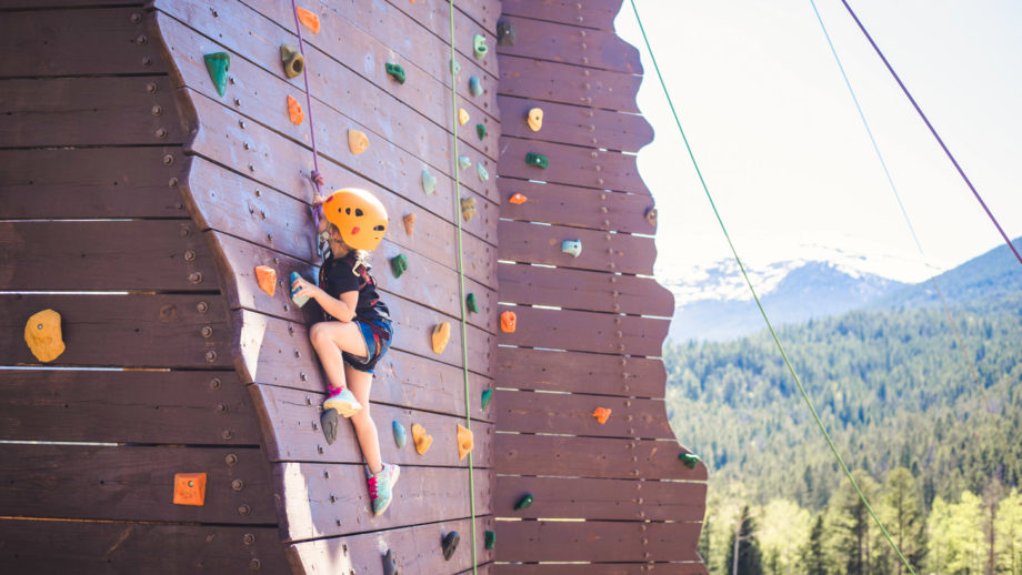 A little girl excelling at climbing the climbing wall.