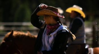 Woman adjusting her cowboy hat while riding a horse.