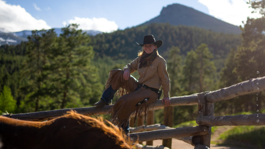A woman balancing on fence wearing a cowboy hat.