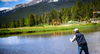 A man fishing into the lake.