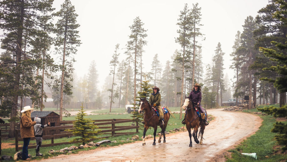 Two women riding horses together in the rain.
