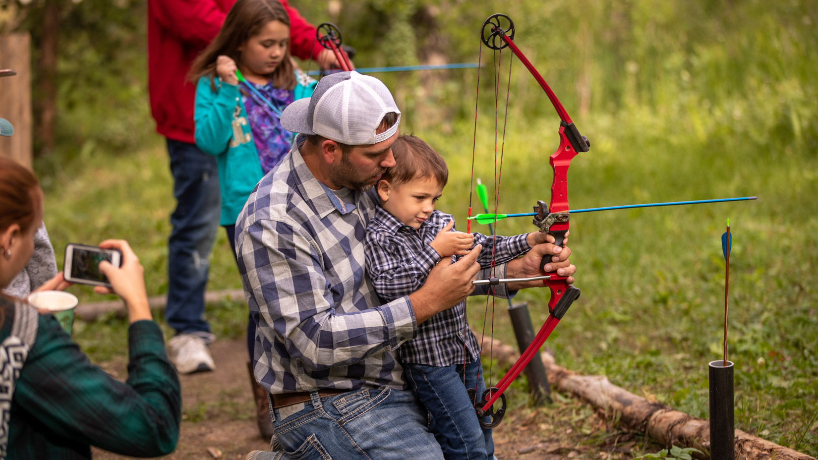 A father helping out a little boy string a boy and arrow.