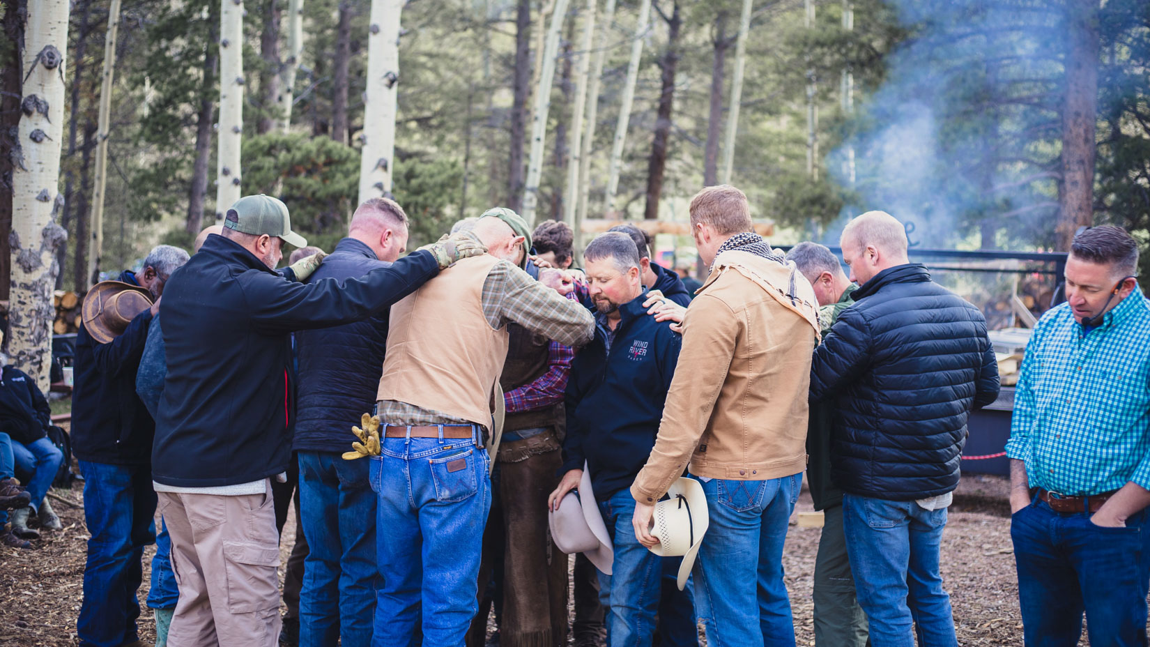 Group huddle of men hugging one another.