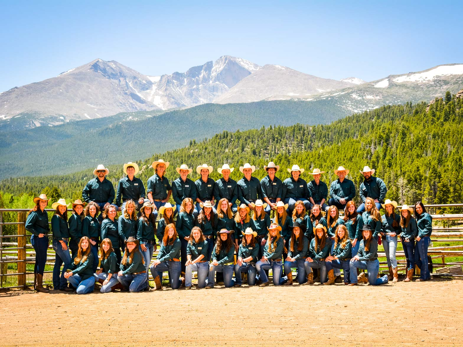 Group photo of young camp staff members in front of a beautiful mountainous landscape.