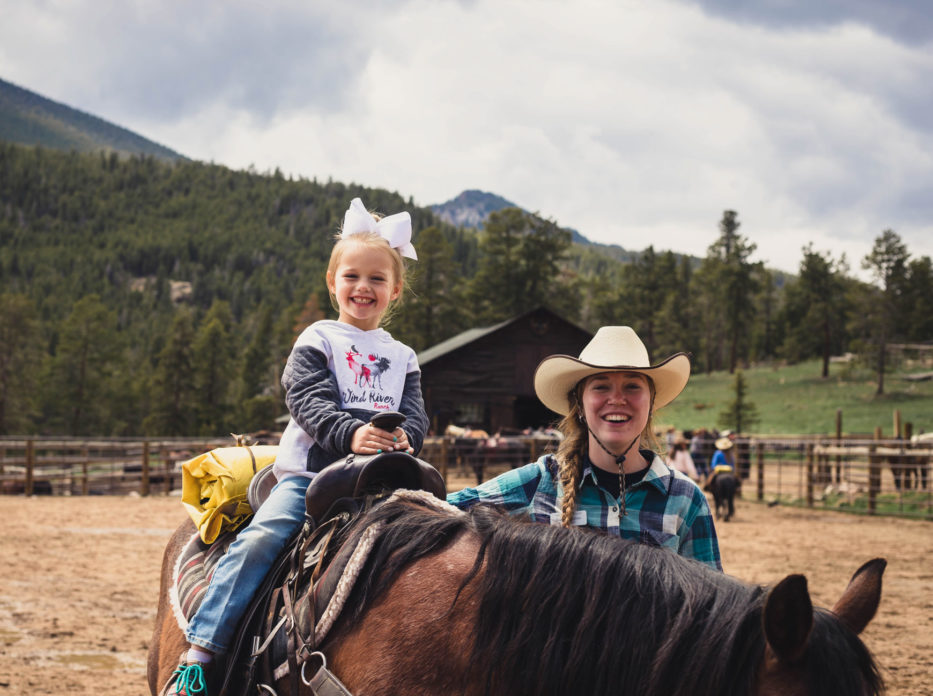 A little girl smiling and riding a horse.