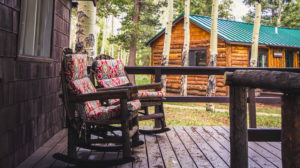 Long's peak cabin front porch of the cabin with two rocking chairs.