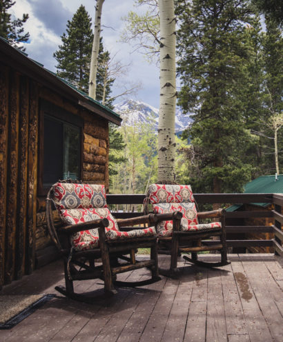 Two chairs on the porch of a cabin.